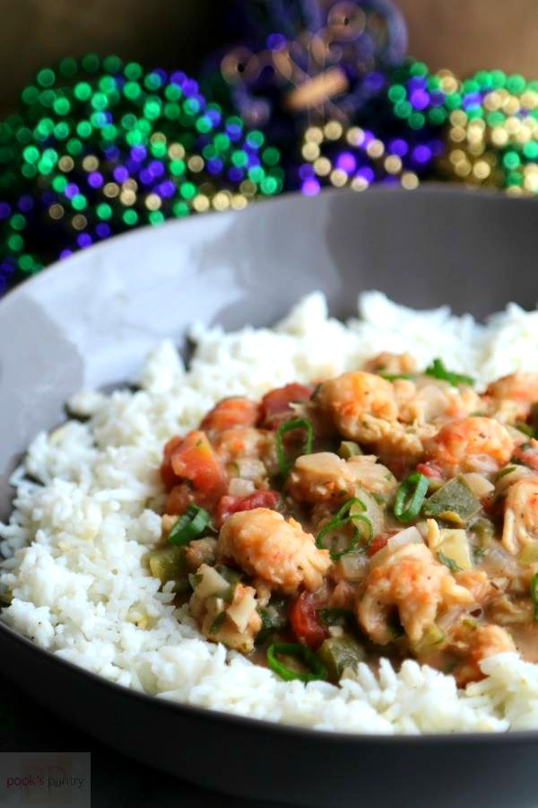 bowl of étouffée with beads in the background