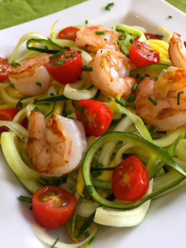 shrimp, zucchini and tomatoes on a white plate