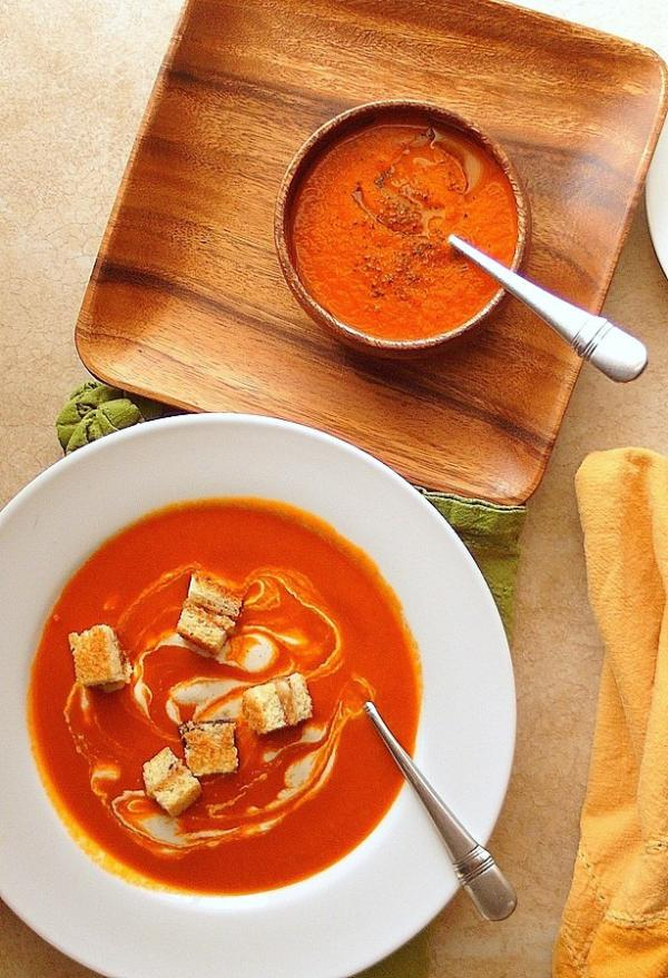 bowls of tomato soup with wooden plate