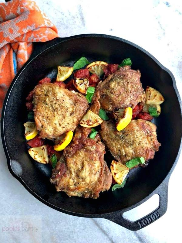 chicken thighs with tomato and lemon in cast iron pan