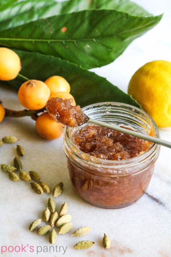 Loquat cardamom jam on spoon with jam jar.