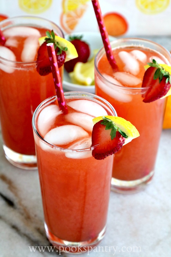 strawberry lemonade iced tea in tall clear glasses with lemon and strawberry garnish