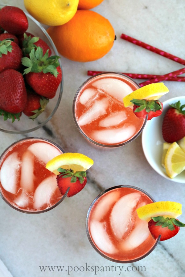 overhead shot of strawberry lemonade iced tea with bowl of strawberries for best summer drinks roundup