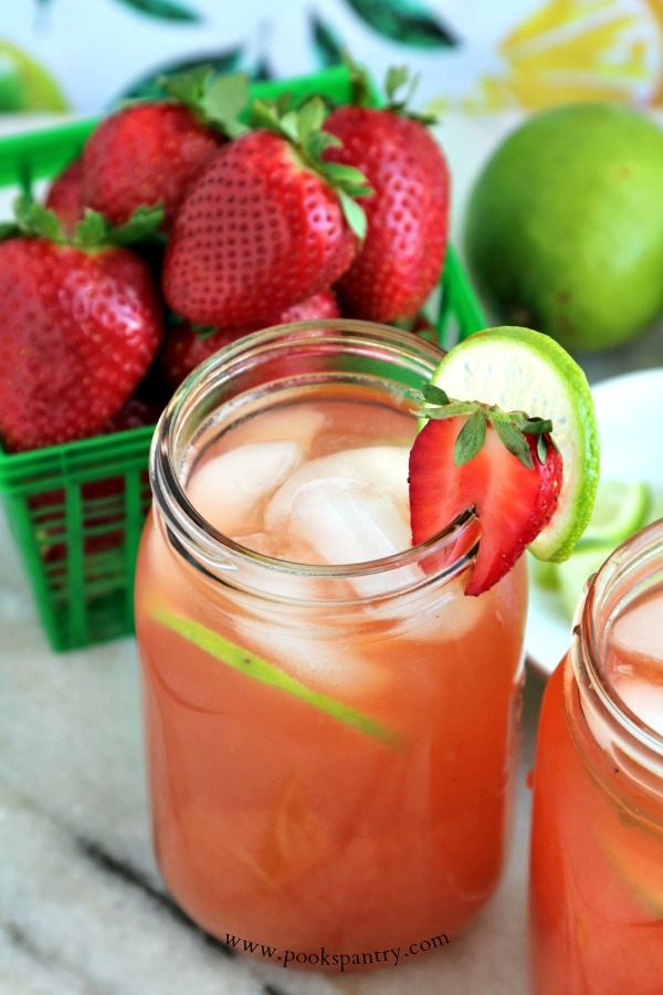 strawberry limeade with limes and strawberries in background