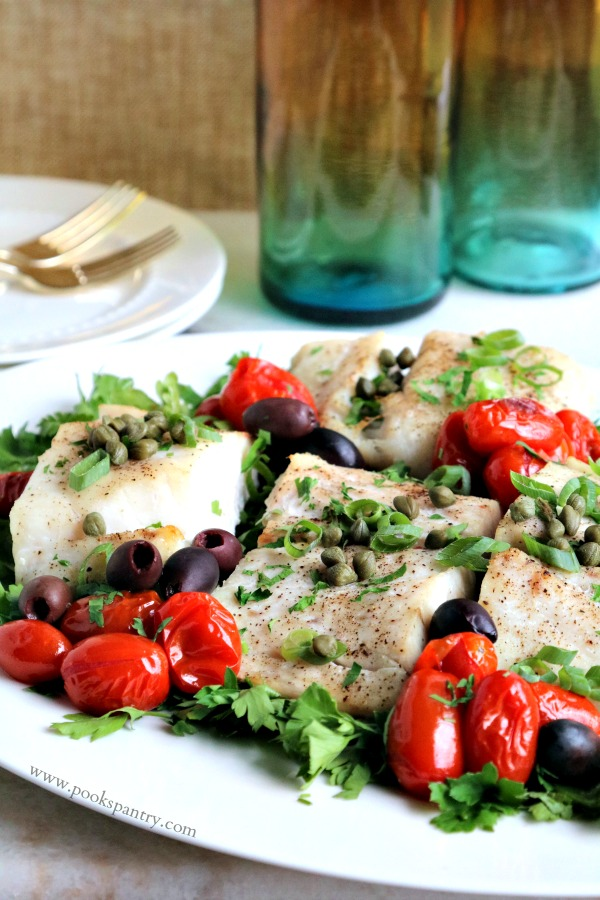 baked corvina on white platter with tomatoes, capers and olives