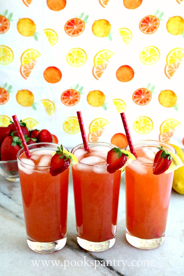 three glasses of strawberry lemonade iced tea with citrus fruits background