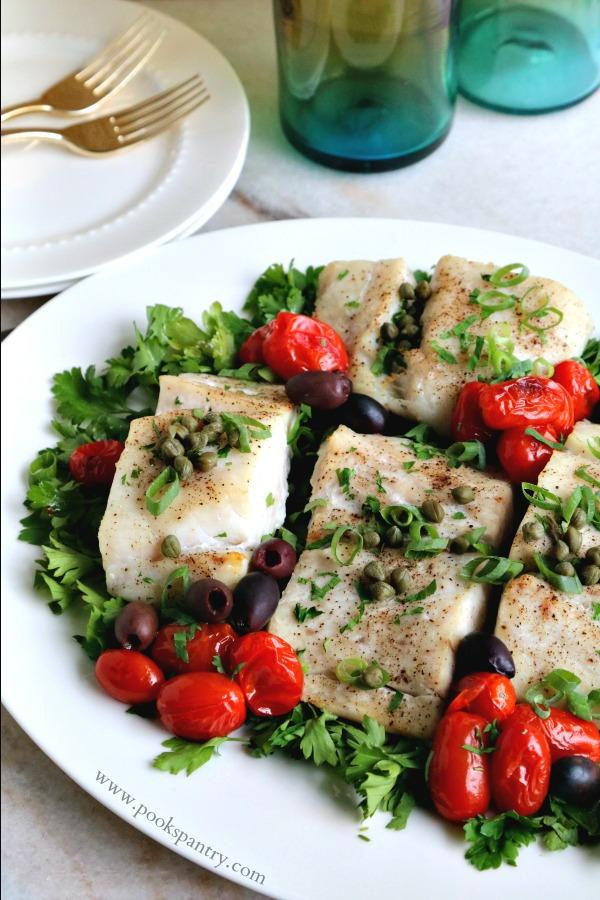baked corvina on white platter with tomatoes and olives