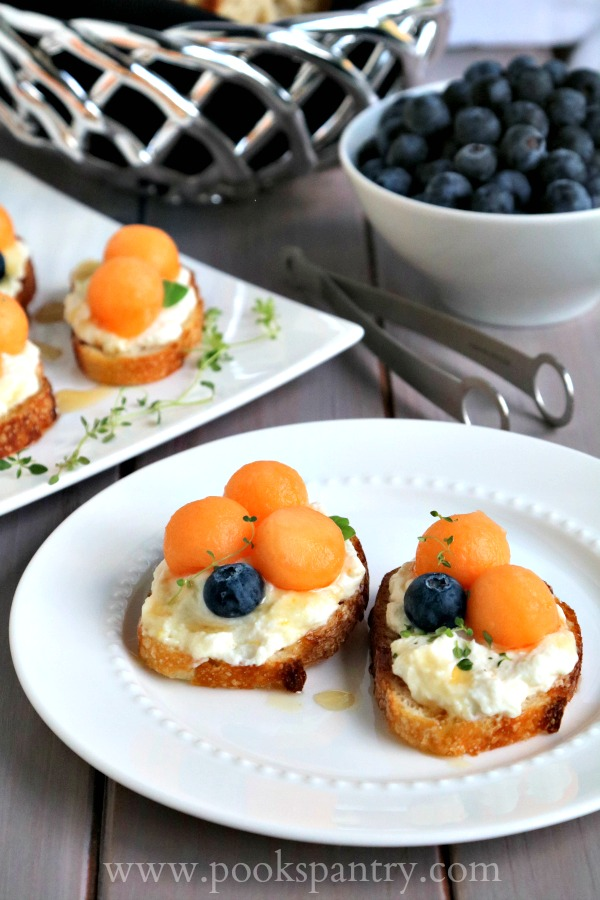 melon and ricotta bruschetta recipe on round white plate with bowl of blueberries in background