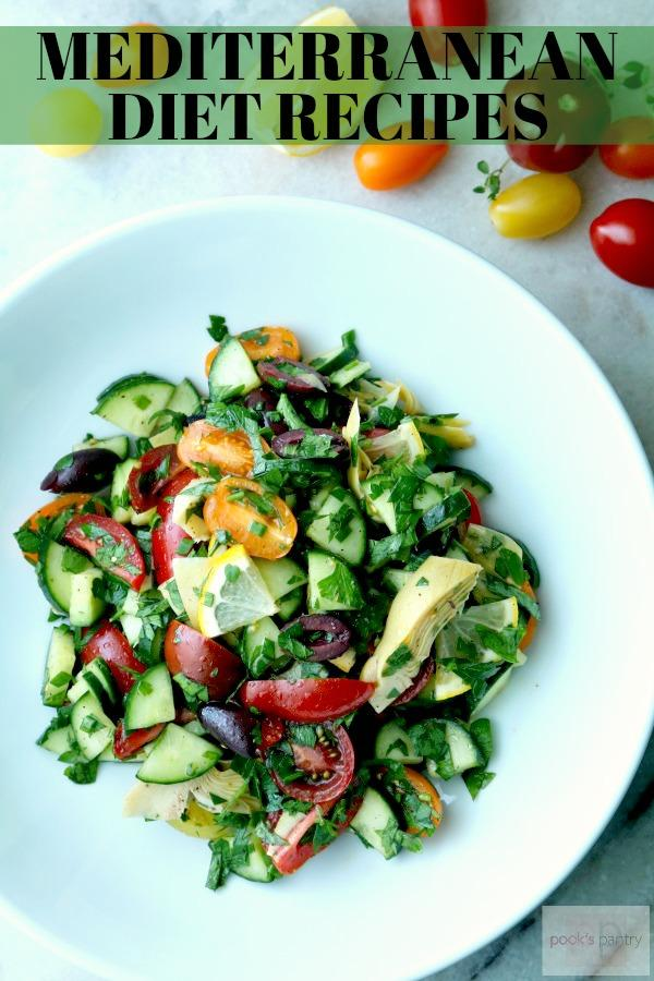 tomato cucumber salad with artichokes, olives and lemon in a white bowl