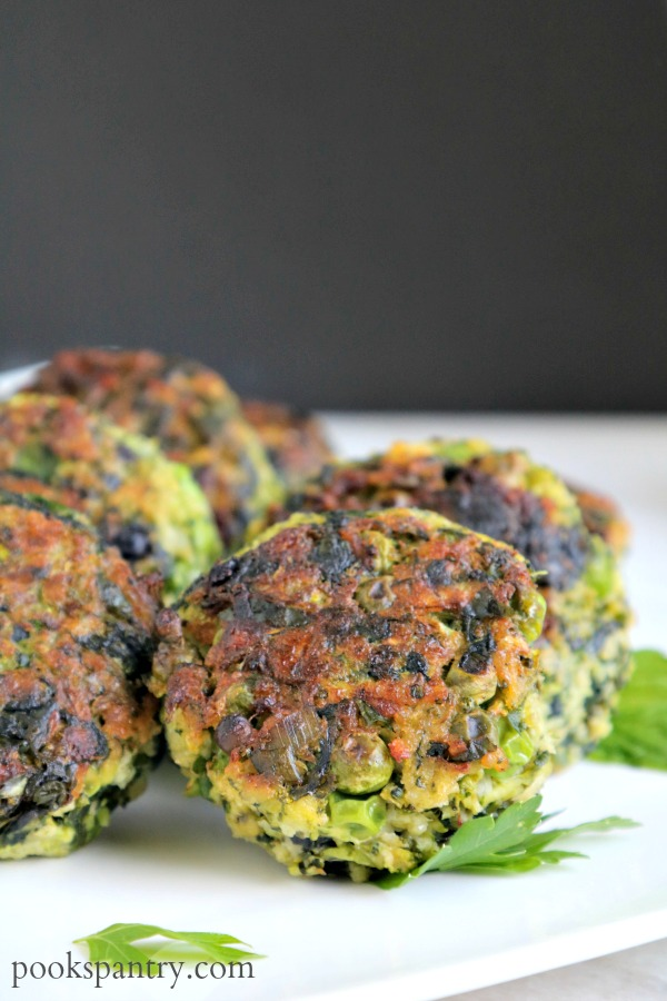 close up of green vegetables cakes on white platter