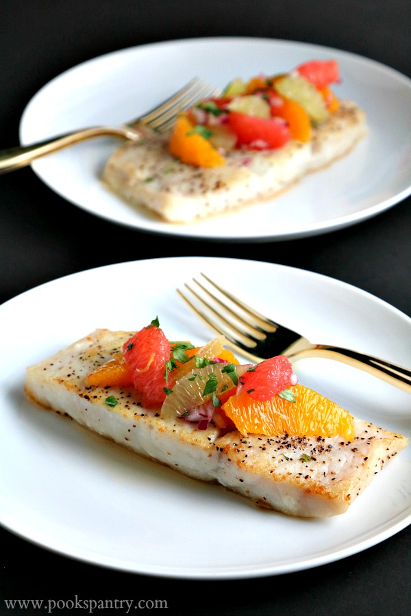 corvina fish recipe with citrus on white plate and black background