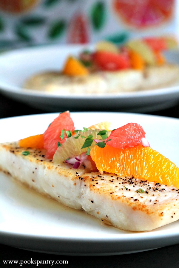 corvina with citrus on white plate with fish in background