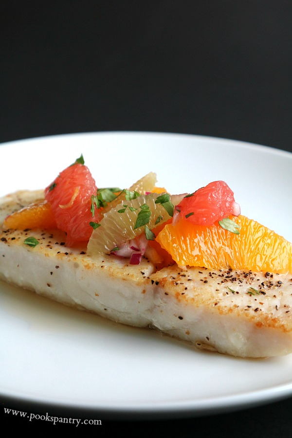 corvina with citrus on white plate and black background