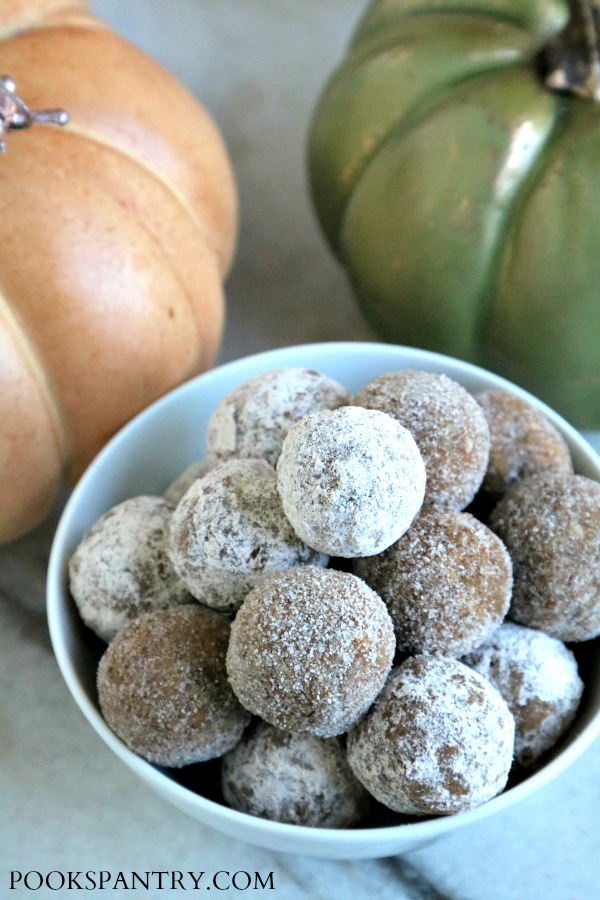 pumpkin rum balls in white bowl with orange and green pumpkins in background