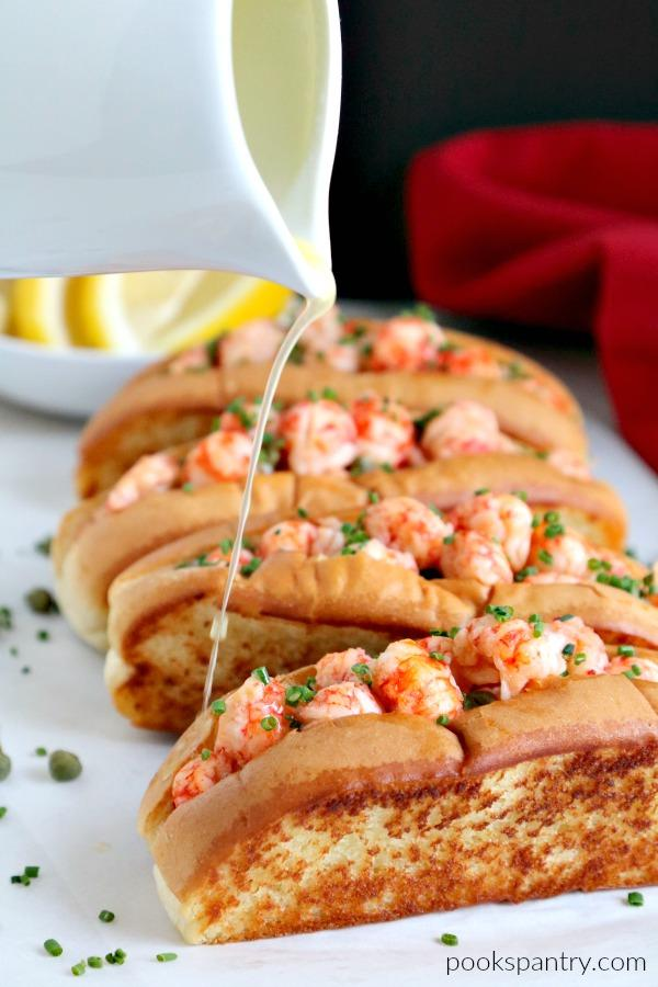 drizzling butter on warm langostino lobster rolls
