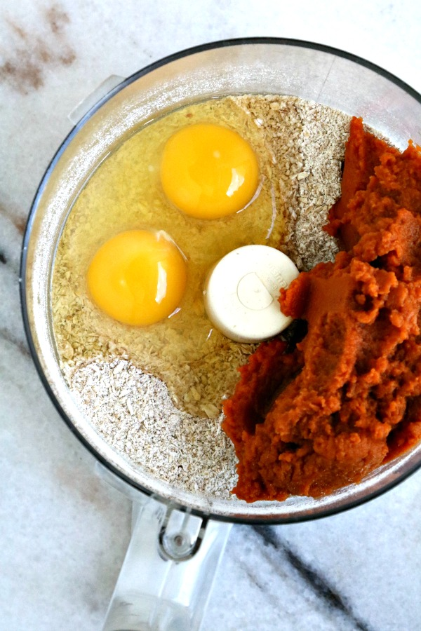 oat flour, eggs and pumpkin in bowl of food processor