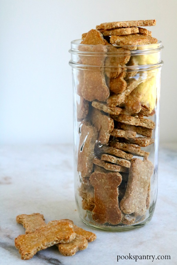 peanut butter banana dog treats in tall mason jar with a few dog treats beside jar