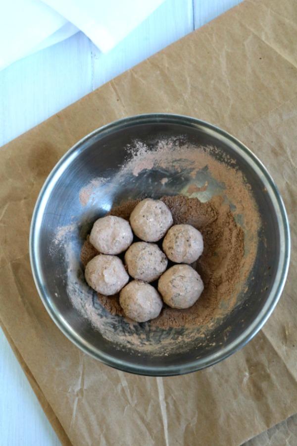 rum balls in cocoa sugar mixture in bowl