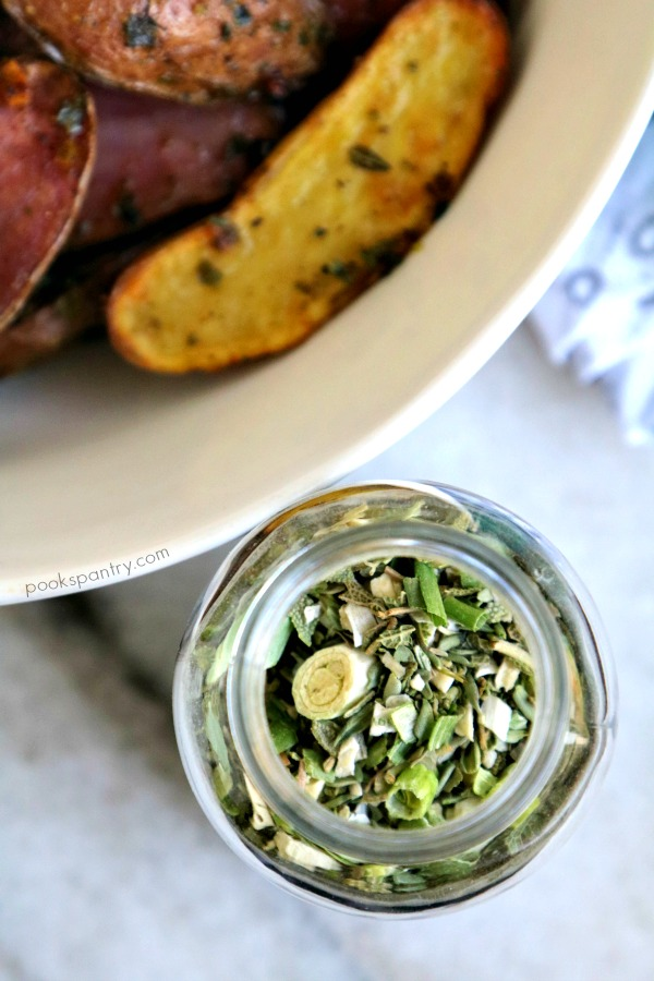 bottle of dried herbs next to bowl of baked fingerling potatoes