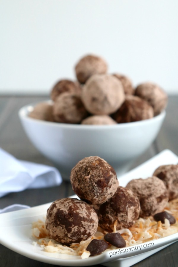 stacked chocolate coconut rum balls with shredded coconut and chocolate chips