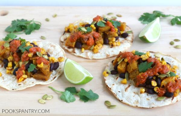 tacos with pumpkin, beans and corn on wooden board