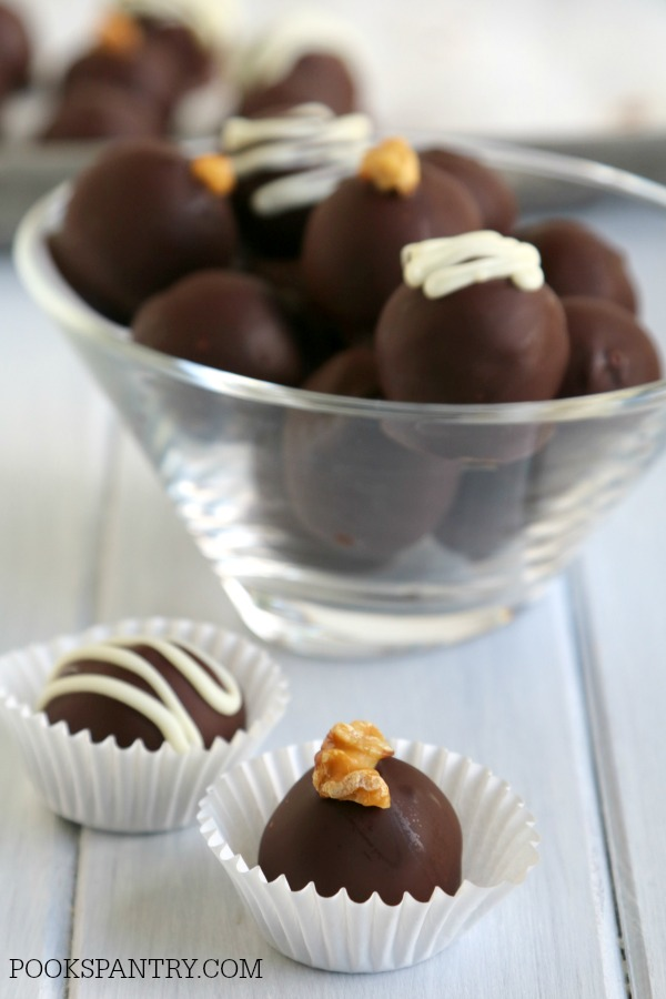 chocolate covered rum balls in white paper candy cups