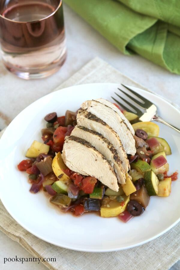 mediterranean chicken and vegetables on white plate with fork