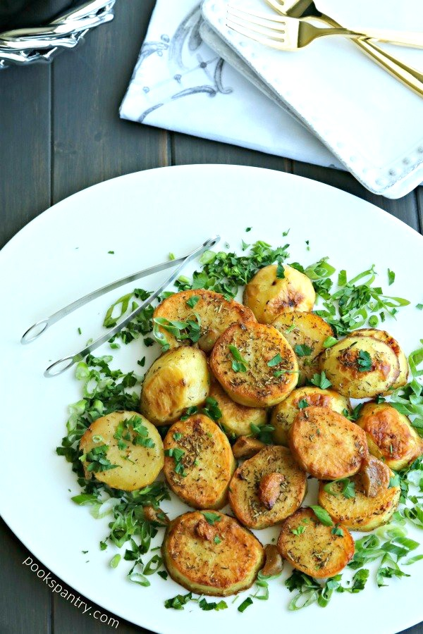 roasted melting potatoes with herbs on white platter