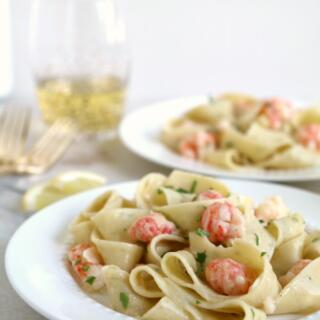 langostino pasta on white plate with gold fork