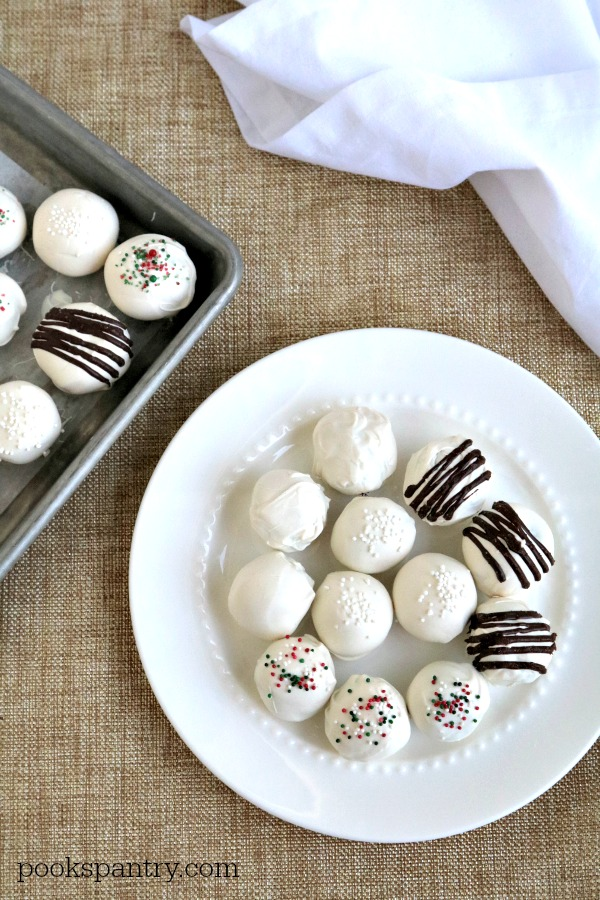white chocolate rum balls on white plate with white napkin in background