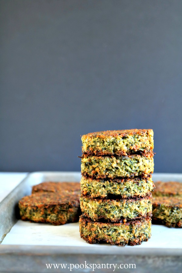 baked broccoli cakes stacked on sheet pan with black background