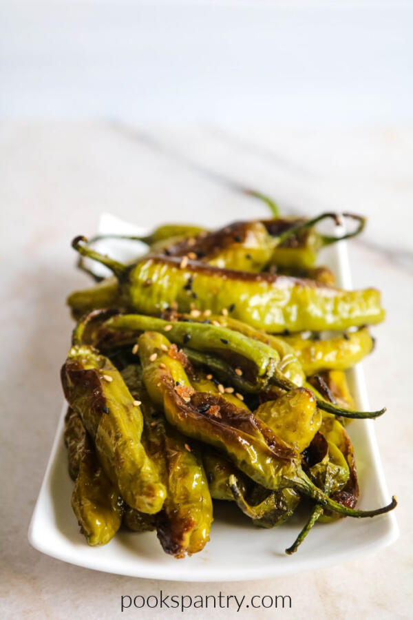 roasted shishito peppers with smoked salt on white plate