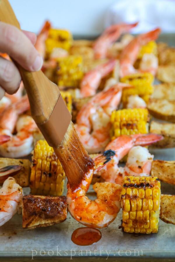 brushing cajun garlic butter on shrimp skewers