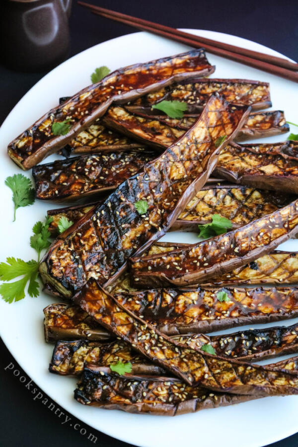 grilled miso eggplant on white platter with herbs