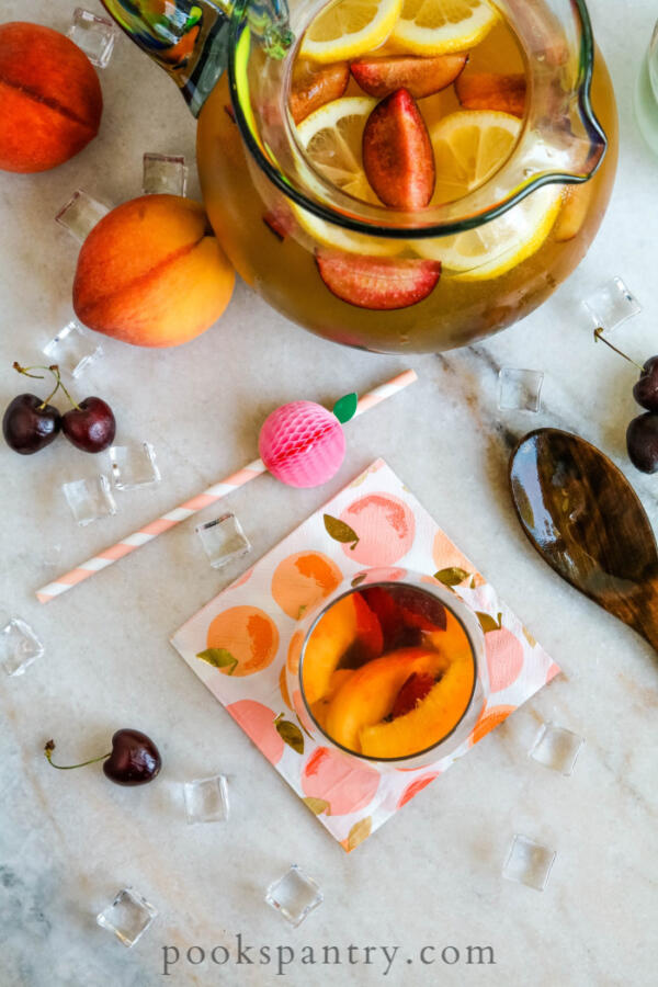 overhead view of white wine sangria with peaches on marble board