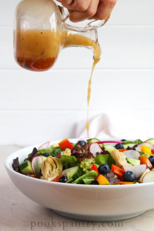 pouring vinaigrette on salad