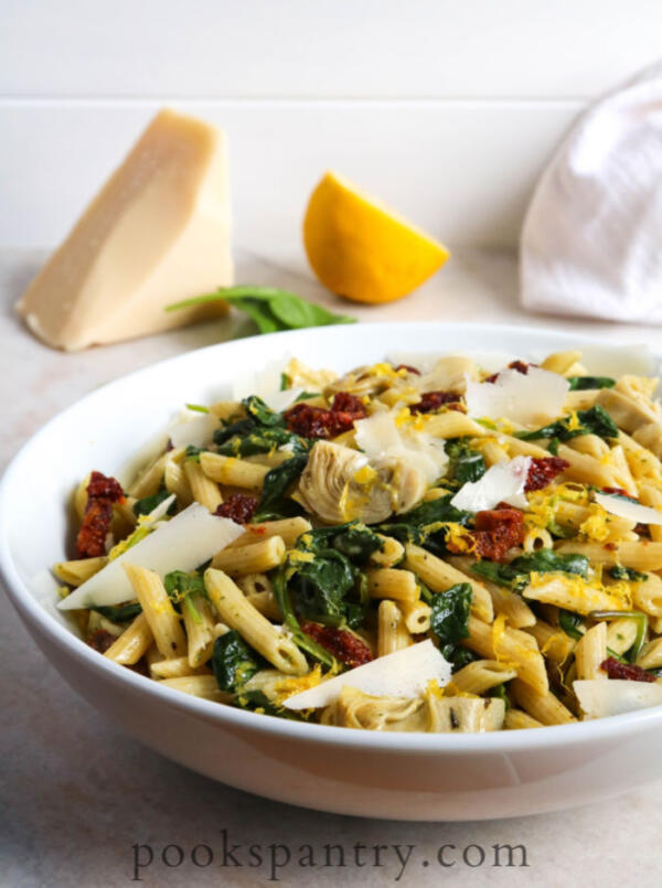 artichoke pasta salad with lemon and spinach in white bowl