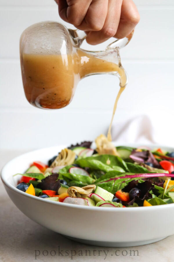 sherry lime vinaigrette on salad in white bowl