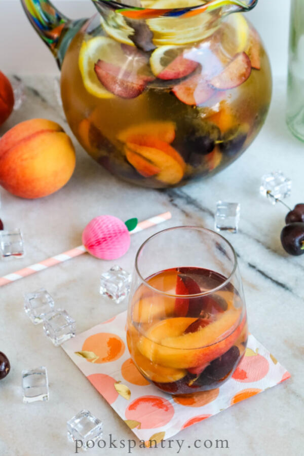 white sangria with peaches in glass and mexican glass pitcher in background