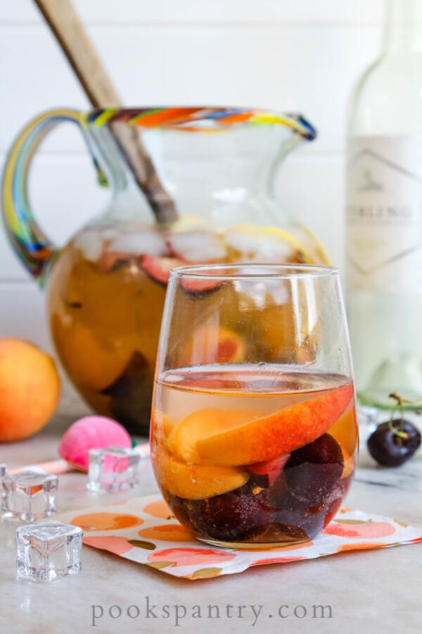 white wine sangria with peaches and cherries in glass on napkin