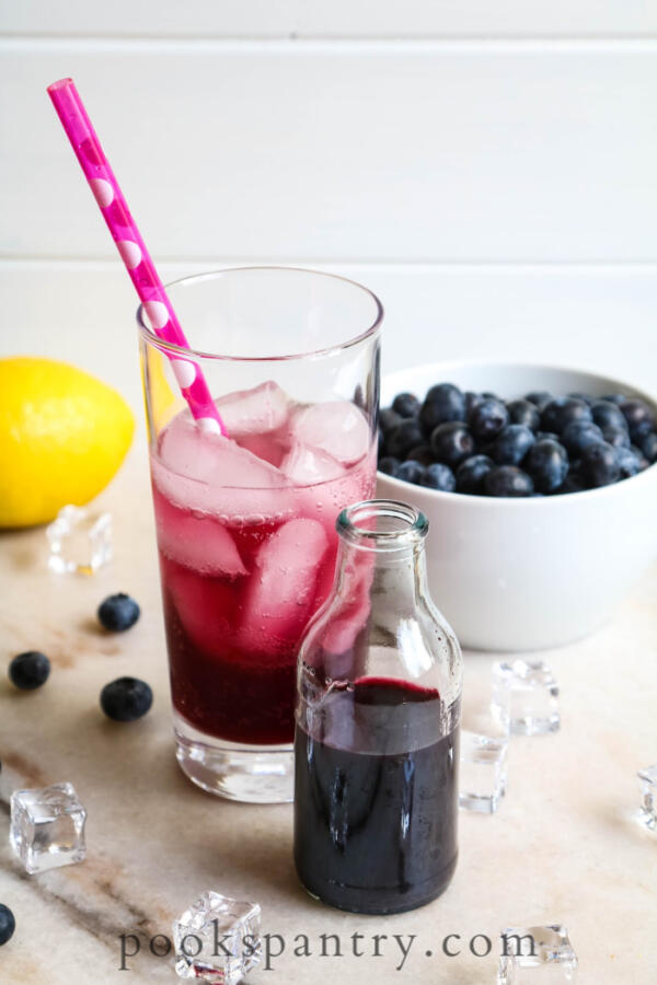 blueberry simple syrup for cocktails with drink in background and bowl of blueberries