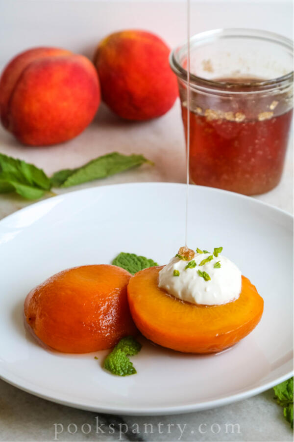 bourbon poached peaches drizzled with bourbon simple syrup on white plate