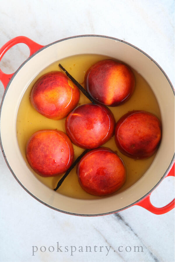 poaching peaches in large pot with vanilla and bourbon