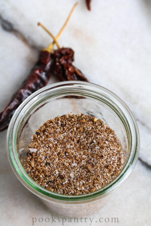 Steak dry rub in glass jar with dried chilies in background.