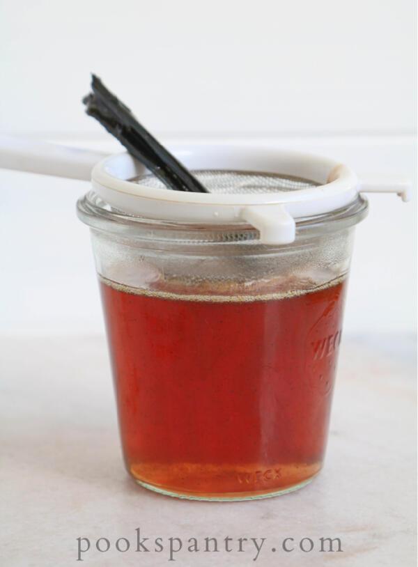 straining peach bourbon syrup