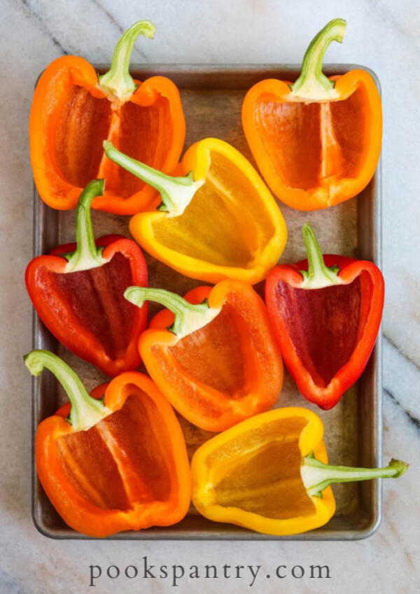hollowed out bell peppers ready to stuff on sheet pan.