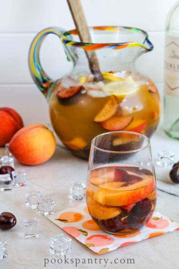 fruity white sangria in glass with pitcher in background
