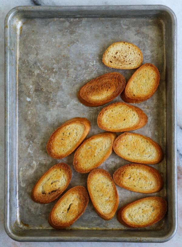toasting crostini for heirloom tomato bruschetta