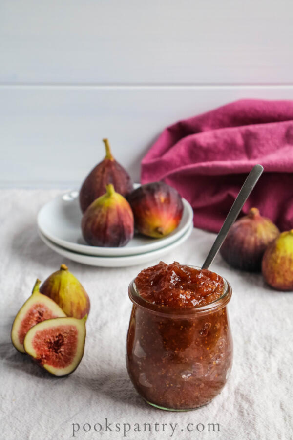 fig jam in glass jar with fresh figs in background