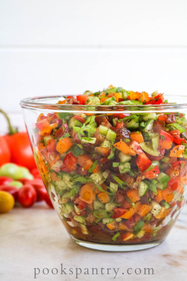 Tomato, cucumber and bell pepper salad in glass bowl